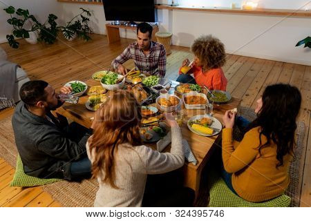 High angle view of a group of young adult multi-ethnic male and female friends sitting around a low table eating Thanksgiving dinner together at home poster