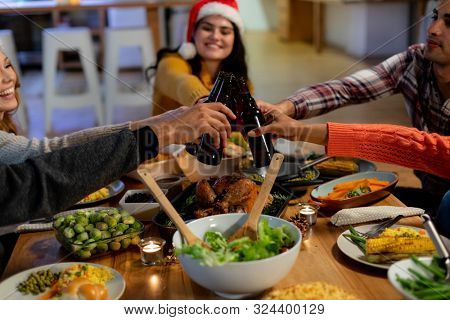 Side view of a group of young adult multi-ethnic male and female friends sitting at a table at home set for Christmas dinner making a toast with bottles of beer, one woman is wearing a Santa hat poster