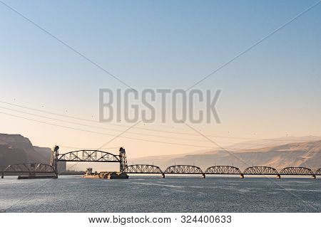 A Cargo Ship Passes Under The Oregon Trunk Rail Bridge On The Columbia River, Oregon, Usa.