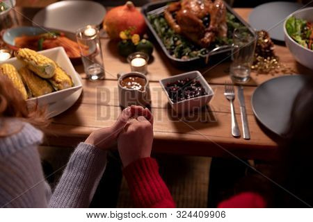 Over the shoulder view of two young adult Caucasian women sitting at a table holding hands saying grace before eating Thanksgiving dinner at home together with friends