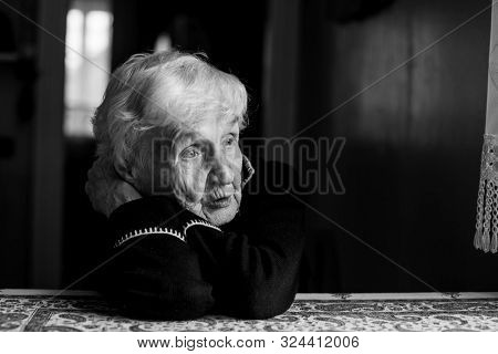 Black-and-white portrait of a sad old woman. Care for lonely pensioners.