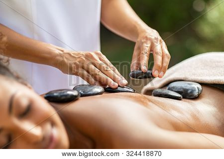 Closeup of masseuse hands placing hot stones on woman back at resort. Masseuse massaging body at spa. Detail of a professional therapist doing lava stones massage on african girl.