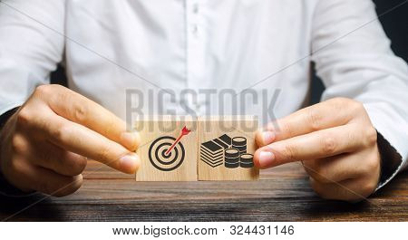 Businessman Collects Wooden Blocks With The Image Of The Goal And Money. The Concept Of Doing Busine
