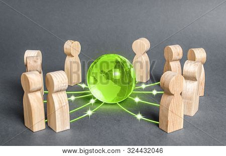 People Surrounded A Green Globe Planet Earth. Cooperation And Collaboration Of People Around The Wor