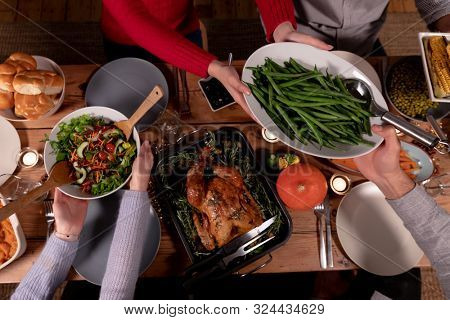 High angle view of a group of young adult multi-ethnic male and female friends sitting around a table holding dishes and serving Thanksgiving dinner at home together