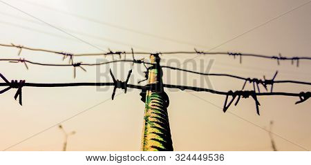 Barbed Wire. Barbed Wire On Fence With Blue Sky To Feel Worrying. The Silhouette Of The Old Barbed W
