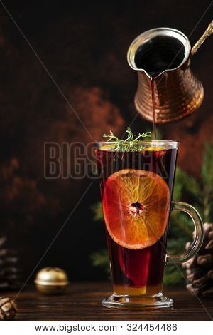 Mulled Wine A Warm Drink Made Of Red Wine, Citruses And Spices In A Glass On A Wooden Table With Chr