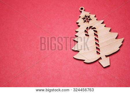 Red Christmas Background. Copy Space. Wooden Christmas Tree Figurine On A Red Background. Copy Space