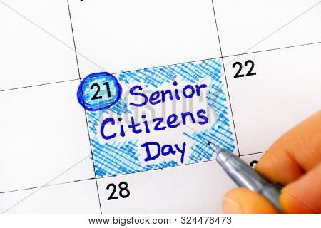 Woman fingers with pen writing reminder Senior Citizens Day in calendar. August 21st. Close-up. poster