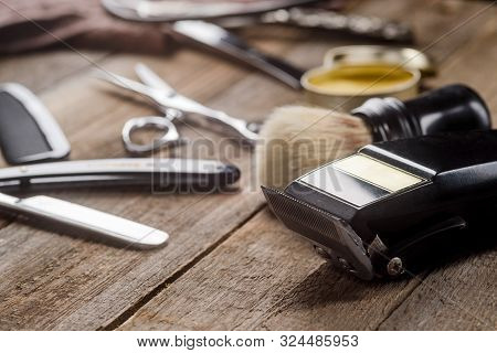 Electric Clipper On The Wooden Surface, Macro. Brush, Scissors, Wax, A Comb, A Straight Razor On The