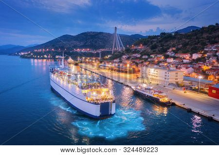 Aerial View Of Cruise Ship At Harbor At Night. Landscape With Ships And Boats In Harbour, City Illum