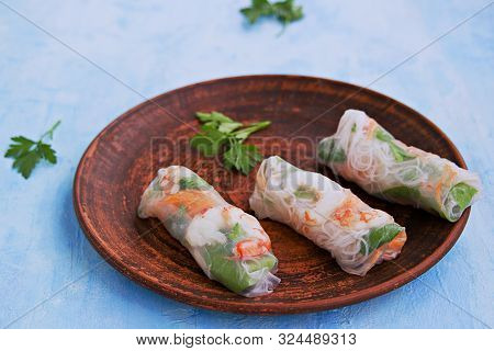 Fresh Spring Rolls In Rice Paper With Shrimp, Vegetables And Rice Noodles On A Brown Clay Plate On A