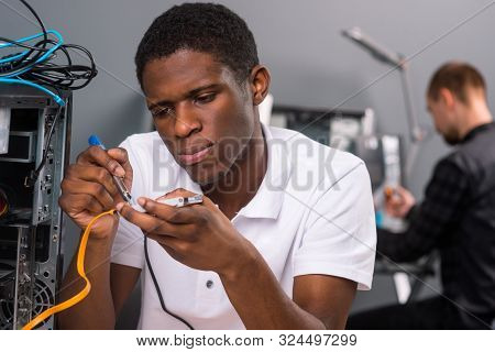 Focused Man Working With A Solderer. Unscrewed Computer And Cords. Another Technician Fixing Somethi