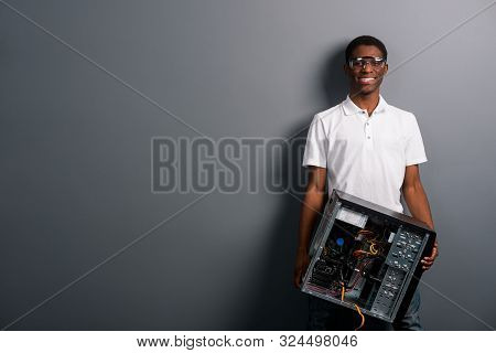 Joyful Male In Protective Glasses Holding An Unscrewed Computer, Grey Background. Place To Insert Yo