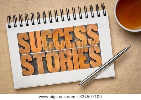 success stories typography - word abstract in vintage letterpress wood type in a spiral sketchbook with a cup of tea, career, business or personal development concept