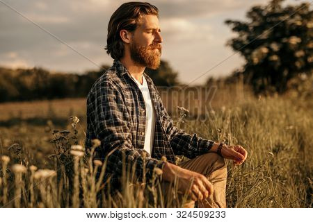 Relaxed Bearded Man With Closed Eyes Sitting In Meadow And Meditating While Establishing Connection