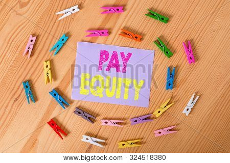 Handwriting text Pay Equity. Concept meaning eliminating sex and race discrimination in wage systems Colored clothespin papers empty reminder wooden floor background office. poster