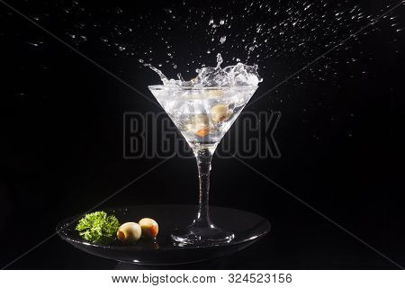 Splashing Martini Cocktail With Green Olives In Drinking Glass On Black Background.
