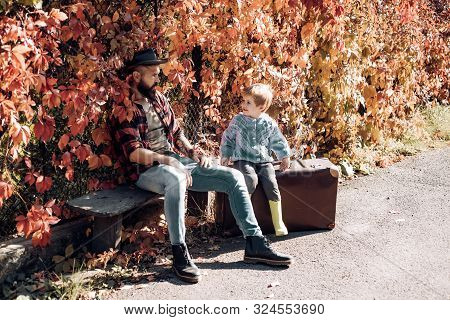 Father with suitcase and his son. Bearded dad telling son about travelling. Traveler with lot experience. Fatherhood and upbringing. Family time. Adventure with son. Telling stories about past times. poster