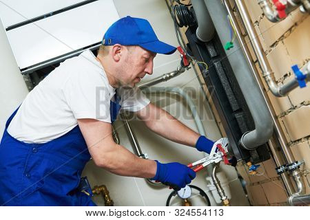 Plumber work. Installing collector for warm water underfloor heating system poster