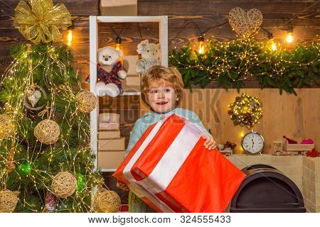 Christmas Kids - Happiness Concept. Little Santa Claus Gifting Gift. Home Christmas Atmosphere. Chee