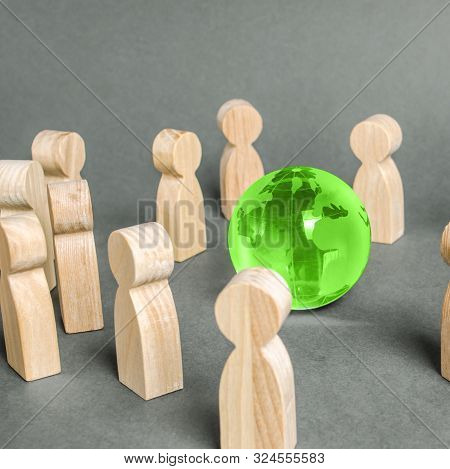 People Surrounded A Green Globe World Planet Earth. Cooperation And Collaboration Of People Around T