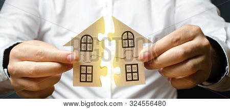 A Man Connects Two Puzzles Into A Whole House Above The Inscription Mortgage. Construction Of Your O