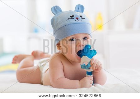 Portrait Of Infant Baby Boy Weared Funny Hat. Kid Lying On Bed And Playing With Teething Toy