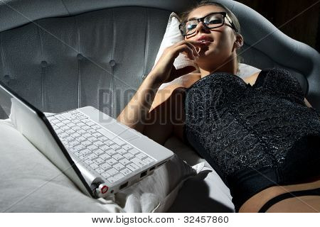Portrait of woman lying on bed with a laptop and play with herself poster