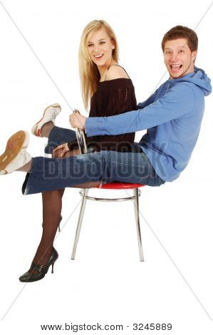 Young Girl And A Guy Sitting On A Chair Together