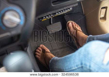 Woman Foot Driving Car With Shoe Pushing On Car Speed Pedal. Female Feet With Brake And Accelerator