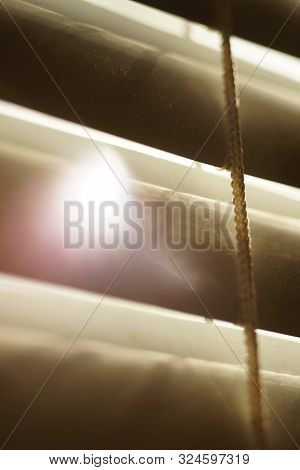 Closed Horizontal Blinds Through Which The Sun Shines