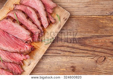 Slices Of Medium Rare Roast Beef Meat On Wooden Cutting Board On Wooden Background. Gourmet Food. Ra