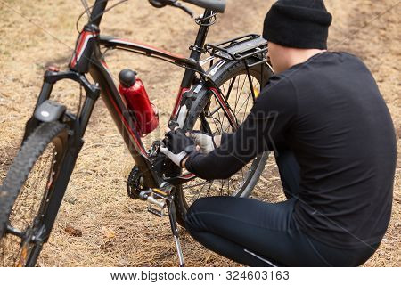 Outdoor shot of man repairing his icycle in field or forest, having puncture of bicycle camera on way, guy posing backwards, squating near his bike, trying to fix it, does sport while hawing free time poster