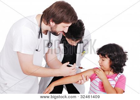 Adult doctor giving injection to young female patient while student is watching poster