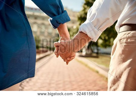 You And Me Forever. Close-up Of Elderly Couple Holding Hands While Walking Together Outdoors