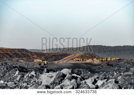 Big Yellow Dump Truck For Ore Transportation On Dark Background. Open Mine Minerals Mining Of Coal,