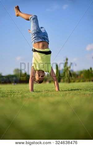 Two Happy Smiling Children Tumbling On Green Grass. Cheerful Brother And Sister Laugh Together. Happ