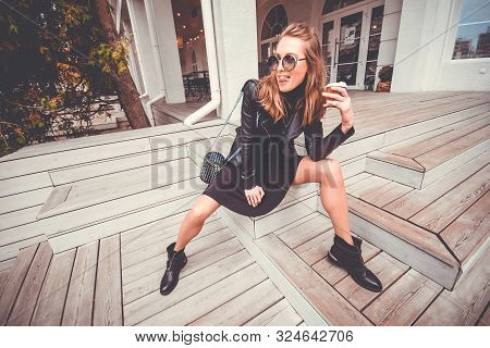Pretty Girl In Glam Rock Style Wear Sitting On A Steps, Drinking Street Coffee And Fooling. Showing