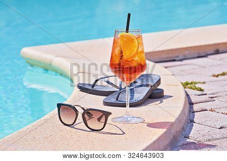 Wineglass Of Cold Cocktail Aperol Spritz Near Swimming Pool With Sunglasses. Traditional Italian Sum