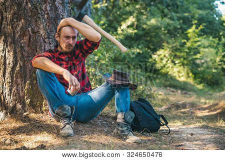 Lumberjack Man Sitting In The Forest. Illegal Logging Continues Today. Lumberjack Worker Standing In
