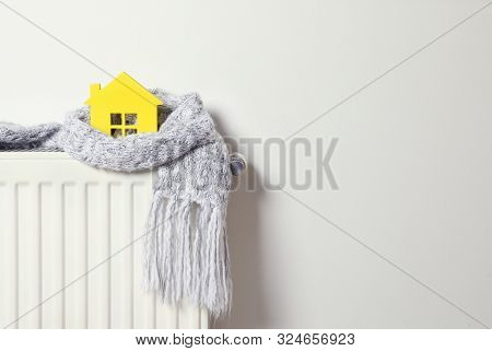 House Model Wrapped In Scarf On Radiator Indoors, Space For Text. Winter Heating Efficiency