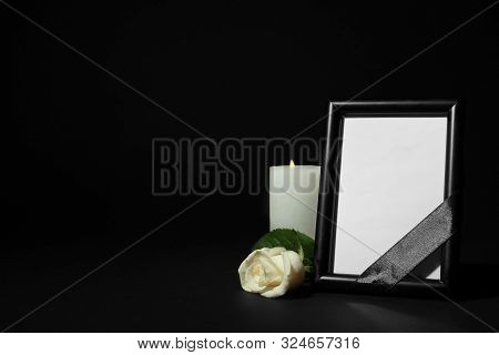 Funeral Photo Frame With Ribbon, White Rose And Candle On Dark Table Against Black Background. Space