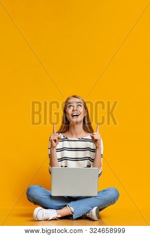 Excited Teen Girl With Laptop Pointing Upwards At Free Space On Yellow Studio Background