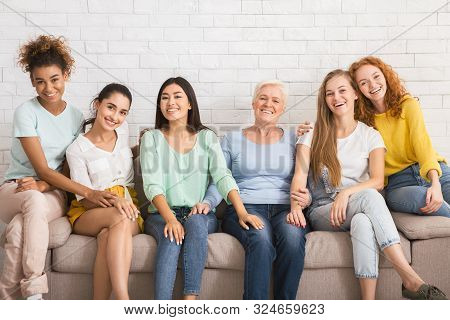 Group Of Diverse Women Smiling At Camera Sitting On Couch Against White Wall Indoor. Equality Concep