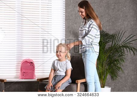 Happy Young Mother Plaiting Her Little Child's Hair At Home. Getting Ready For School