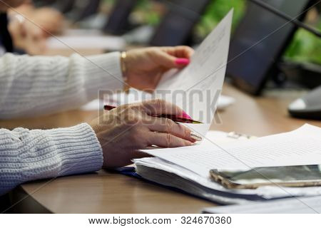 A Woman With Multi-colored Manicure Is Sorting Through Papers While Sitting At Her Desk During A Mee
