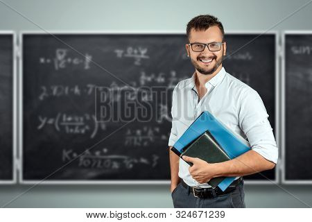 Portrait Of A Young Male Teacher On The Background Of The School Blackboard. Teacher's Day Knowledge