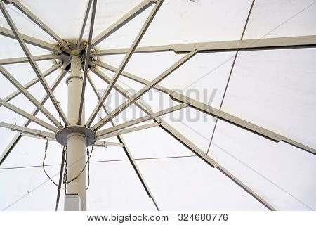 Large Market Or Gastronomy Parasol With White Fabric And Metal Struts, Which Are Opened By Motor Dri