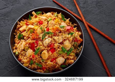 Schezwan Chicken Fried Rice In Black Bowl At Dark Slate Background. Szechuan Rice Is Indo-chinese Cu